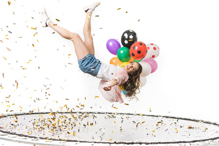 smiling girl holding colorful balloons and falling on trampoline isolated on white Standard-Bild