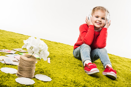 adorable little child listening music with headphones while sitting on green carpet isolated on white Stock Photo