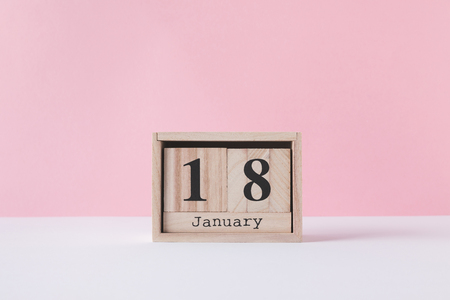close up view of wooden calendar isolated on pink Stockfoto - 112540007
