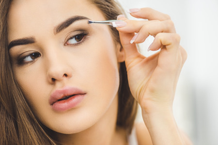 portrait of young woman plucking eyebrows with tweezers Stockfoto