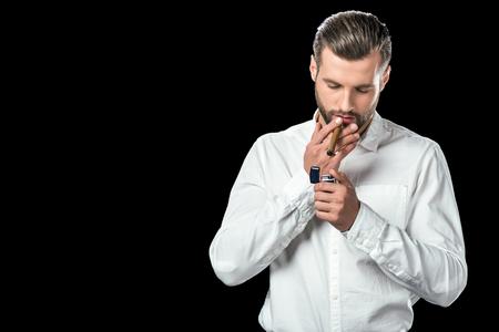 handsome man lightning cigar with lighter, isolated on black