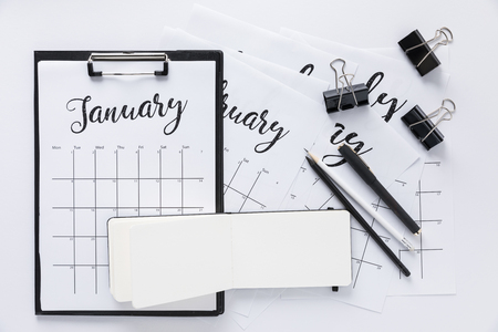 top view of arrangement of office supplies and calendar isolated on white