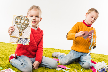 focused little sisters making diy greeting cards while sitting on floor isolated on white