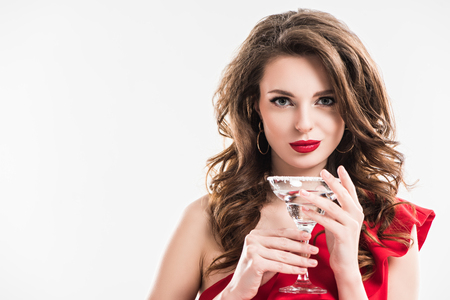 fashionable girl in red dress holding glass of cocktail isolated on white Stockfoto