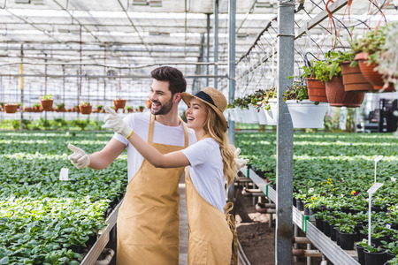 Blonde woman and handsome man in aprons talking among flowers in glasshouse
