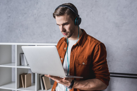 young handsome man in headphones working with laptop