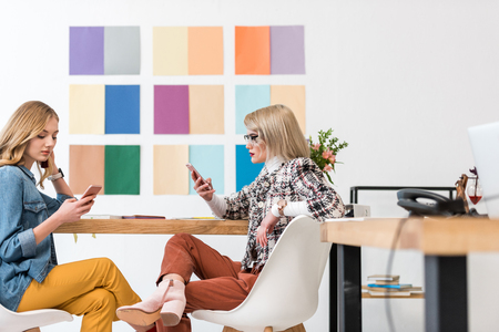 fashionable magazine editors working with smartphones at workplace with color palette on wall