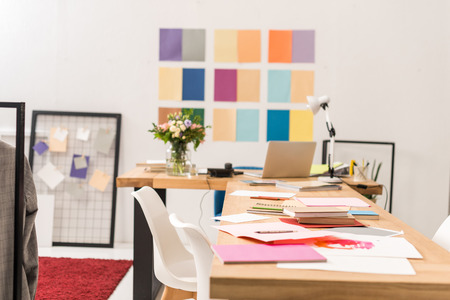 documents at workplace in fashionable modern office with color palette on wall 写真素材 - 112539386