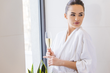 portrait of beautiful woman in bathrobe with glass of champagne at home