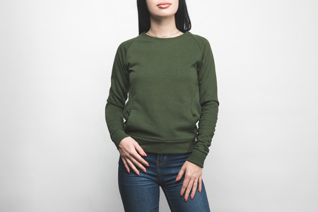 cropped shot of young woman in blank green sweatshirt on white