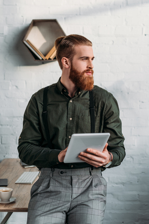 bearded businessman holding tablet and looking away Stock Photo