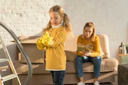 child wearing rubber gloves while cleaning room and mother reading book on sofa after relocation