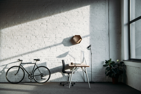 bicycle and working table with computer in office