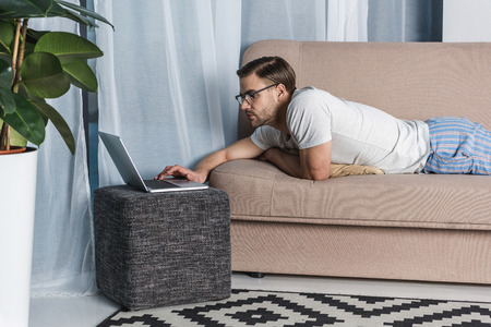 young attractive freelancer in pajamas working with laptop on couch Banque d'images