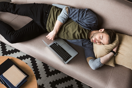 high angle view of overworked man with laptop sleeping on couch Stock Photo