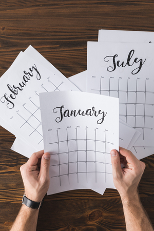 partial view of man holding calendar in hands at wooden table Stockfoto - 112538449