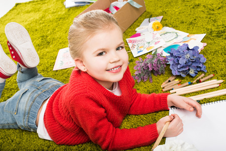 smiling  little child drawing with color pencils on green soft carpet