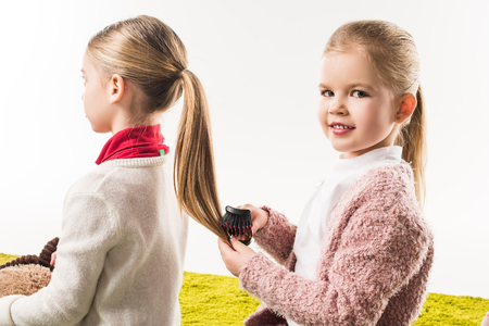 beautiful child brushing hair of sister while sitting on floor isolated on white