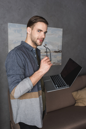 young stylish businessman with laptop at modern office Stock Photo