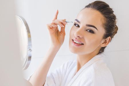 young woman plucking eyebrows with tweezers Stock Photo