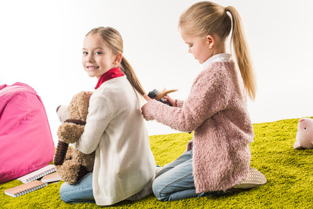adorable child brushing hair of sister while sitting on floor isolated on white Stockfoto