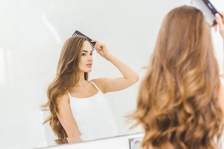 Belle femme se brosser les cheveux avec un peigne dans la salle de bain Banque d'images