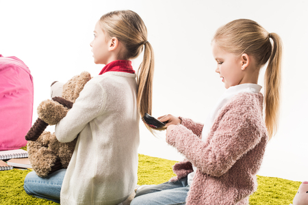happy child brushing hair of sister while sitting on floor isolated on white