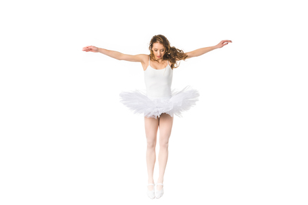young ballerina with open arms jumping and looking down isolated on white