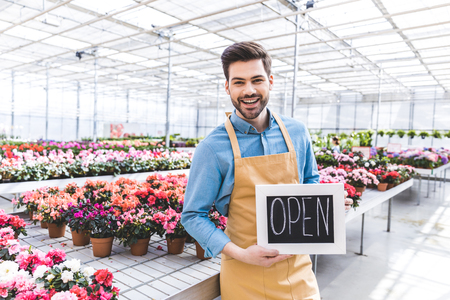 Male owner of greenhouse with Open board by flowers Фото со стока - 112538867