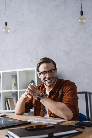 happy young designer sitting at workplace in modern office Stock Photo