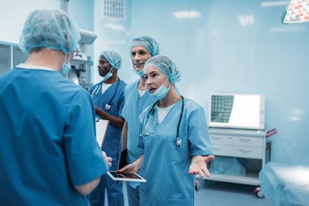 four multiethnic surgeons talking in operating room 写真素材