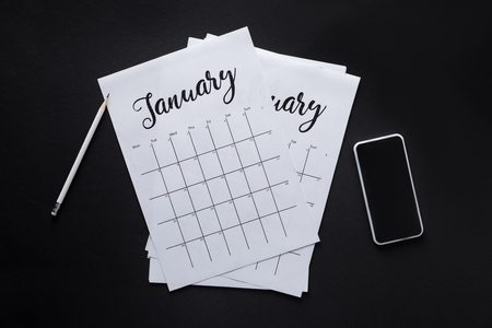 flat lay with paper calendar, smartphone and pencil isolated on black Stockfoto