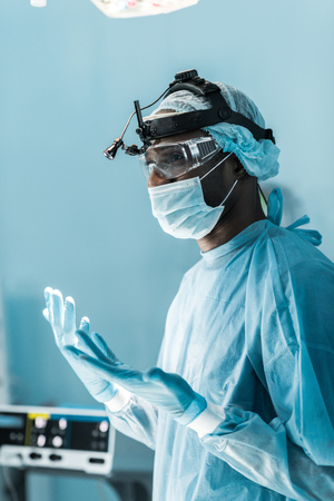 side view of african american surgeon in medical gloves in operating room Stock fotó - 112540135