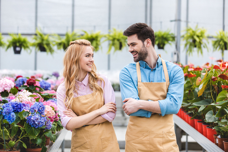 Man and woman owners of glasshouse among flowers Stock Photo