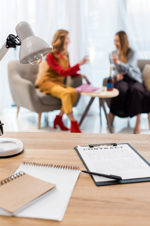 selective focus of businesswomen working in modern office, contract and documents on table on foreground