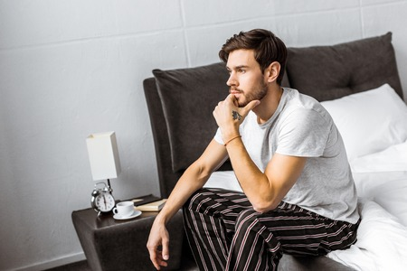 thoughtful young man in pajamas sitting on bed and looking away in the morning 版權商用圖片 - 112607477