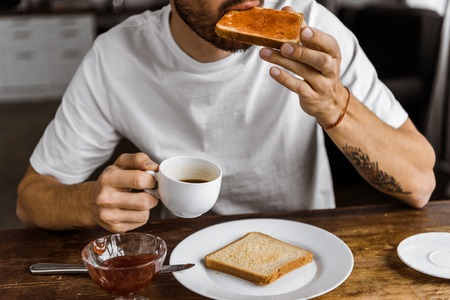 cropped shot of young man eating toast with jam and drinking coffee at home