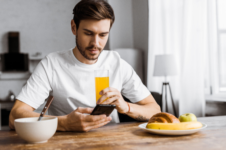 handsome young man using smartphone during breakfast at home