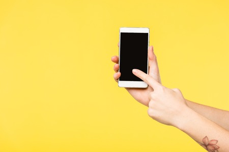cropped shot of person holding smartphone with black screen isolated on yellow 스톡 콘텐츠