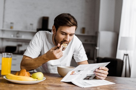 young man having cereal for breakfast and reading newspaper at home