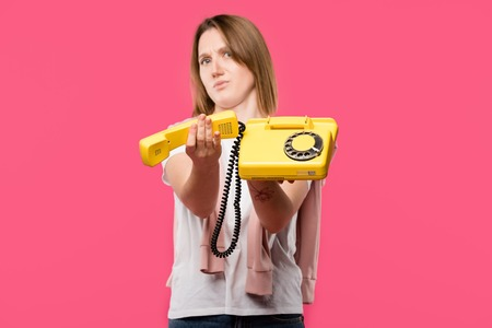 young woman with frowning face holding yellow rotary phone isolated on pink Stock Photo