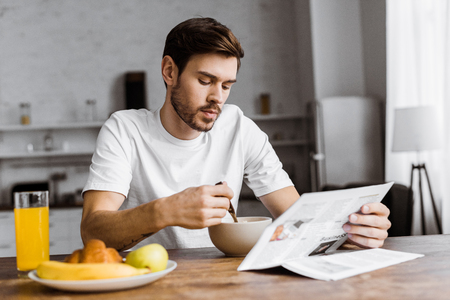 handsome young man having breakfast and reading newspaper at home Stock Photo