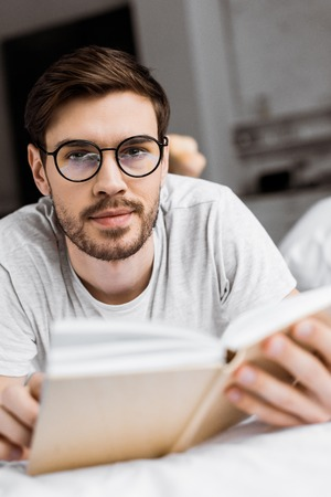young man in eyeglasses holding book and looking at camera while lying on bed 版權商用圖片 - 112607831