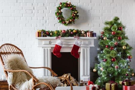 woonkamer met open haard, schommelstoel en versierde kerstboom Stockfoto