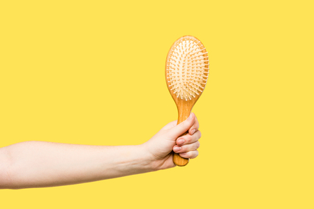 cropped shot of person holding hairbrush isolated on yellow Foto de archivo - 112607840