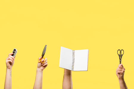 cropped shot of male and female hands holding scissors, stapler and blank notepad isolated on yellow 版權商用圖片