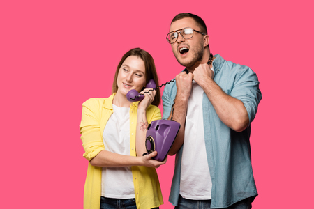 smiling young woman talking by handset while man with wire around neck screaming isolated on pink