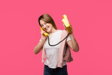 cheerful young woman talking by rotary phone and laughing isolated on pink