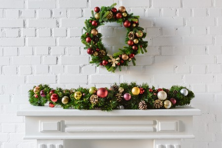festive christmas wreath over fireplace mantel with white brick wall