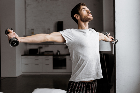 handsome young man in pajamas training with dumbbells and looking up at home